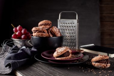 Chocolate cookies on dark wooden and blackboard background