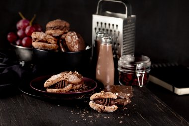 Christmas almond cookies and chocolate milkshake on dark wooden