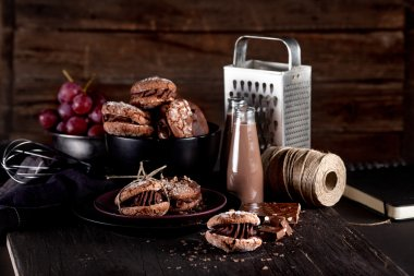 Organic almond cookies on dark wooden background with chocolate