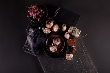 Maroni cookies, grapes and chocolate milkshakes on dark wooden b