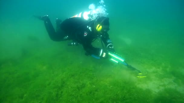 Diver with the metal detector searching for underwater treasure