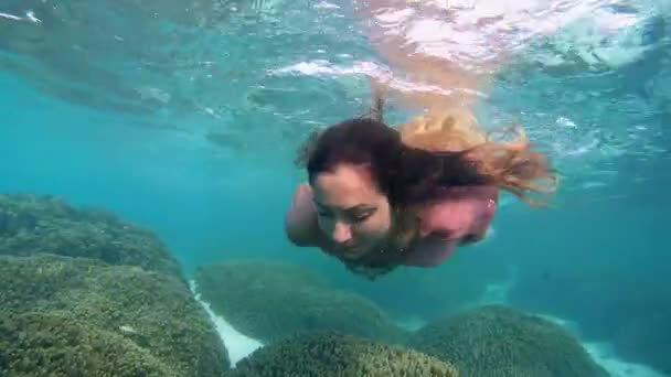 Young beautiful girl in dress posing submerged under water on coral feef, Indian Ocean, Maldives