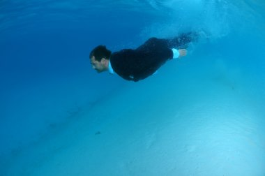 The groom in a suit dives into the underwater, Indian Ocean, Mal