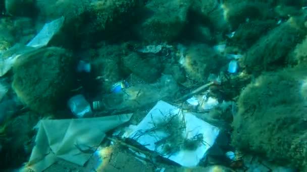 Zpomalený pohyb, detailní záběr plastového znečištění mořského dna, Tropické ryby plavou přes mořské dno pokryté spoustou plastového odpadu. Láhve, sáčky a jiné plastové trosky na mořském dně na Jadranu