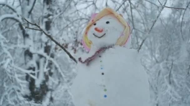 Boldog vicces hóember-nő, a háttérben egy erős hóesés. Odessza, Ukrajna