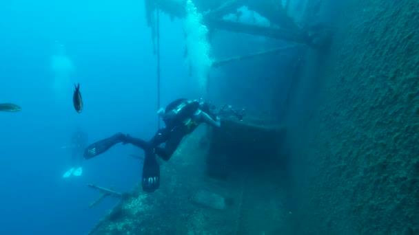 MEDITERRANEAN SEA, KYPR - AUGUST, 2021: Potápěčský fotograf fotografuje záchranný člun na vraku švédského trajektu MS Zenobia. Vrak potápění. Středozemní moře, Kypr