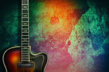 Old, jazz electric guitar on a multicolored grunge background. Copy space. Background for music festivals, concerts. Musical education. Concert concept. Musical instruments.