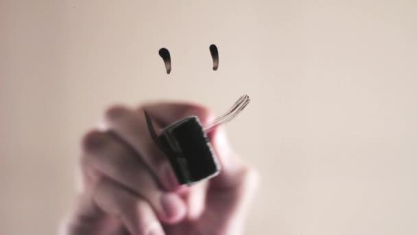 Ruční kresba usmívající se tvář na skle. Ruční kresba veselé a smutné smajlíky na sklo
