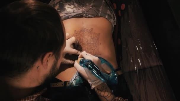 Tetováló mester a szakáll, hogy egy tetoválás minta mandala. Válla mögül lövés