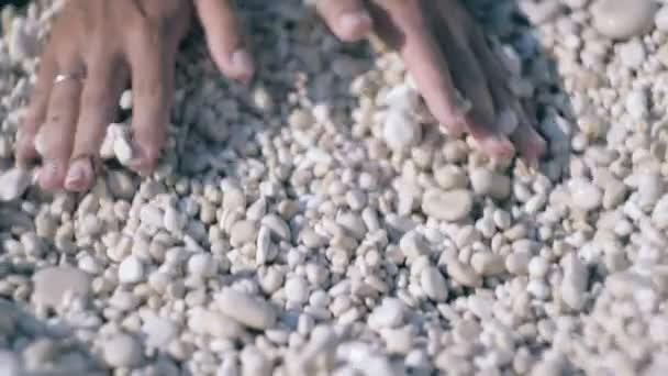 Žena, ruce drží a relase malé kameny v rukou na pláži kamenné pozadí