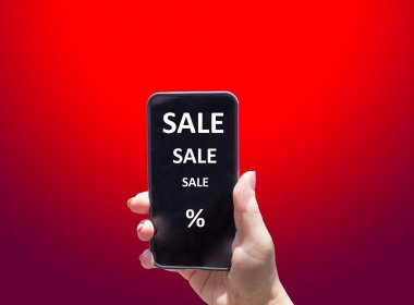 The phone with text SALE in female hand on the red background