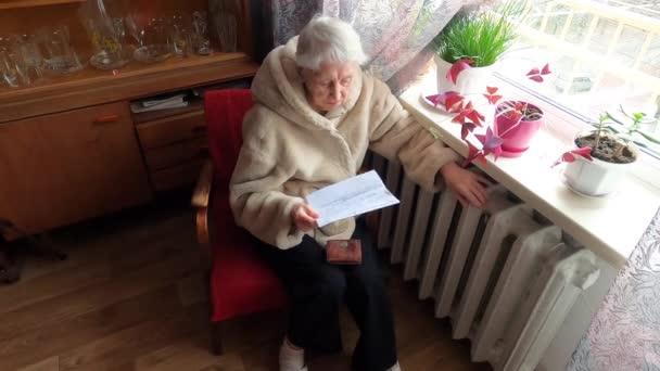 Die Seniorin mit der Gasrechnung vor dem Heizkörper. Zahlung für Heizung im Winter.