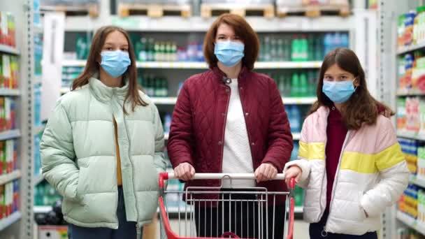 Matka a dcery s nákupním vozíkem v supermarketu během pandemie