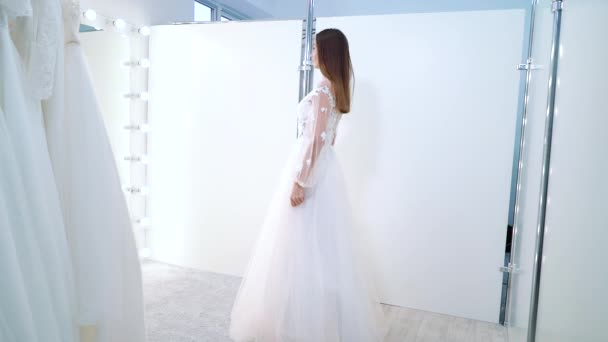 Fiatal nő próbál esküvői ruha menyasszonyi szalonban