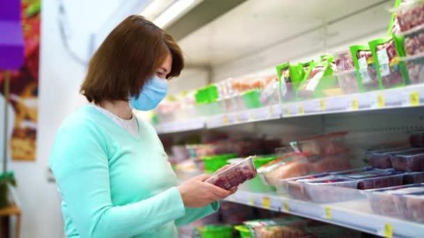 Žena nakupující syrová játra v supermarketu během pandemie