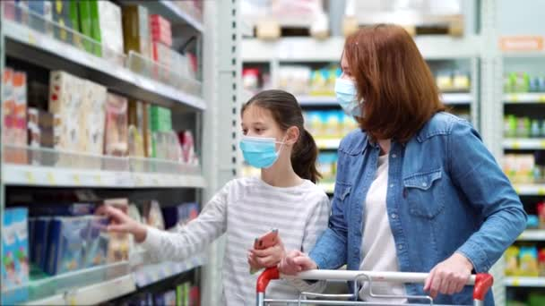 Mother and daughter in masks in sweets department in supermarket