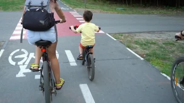Rodina na kolech projíždějících červeným přejezdem