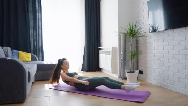 Žena dělá břišní cvičení doma