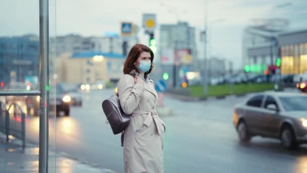 Žena v masce čeká večer na autobus