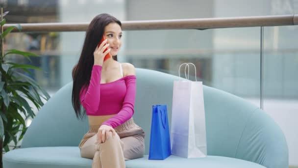 Szexi nő beszél telefonon vásárlás után