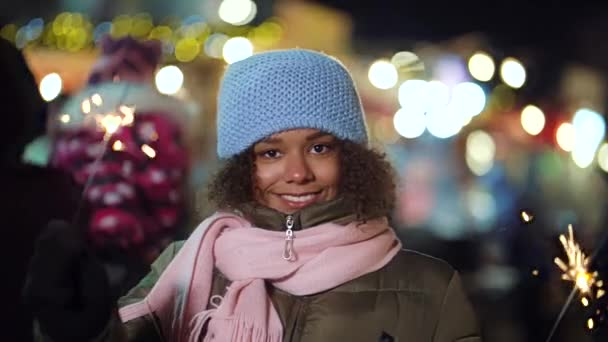 Black girl playing with sparklers on Christmas market