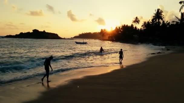 Západ slunce na ocean beach, lidé pěšky podél vody, těší teplý letní večer
