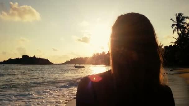 Magányos lány nézte a naplementét a tropical beach, viharos óceán hullámai partra