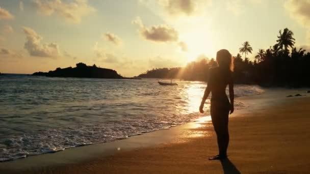 Magányos nő állt üres tengerparton naplementekor, nézte a viharos óceán hullámai