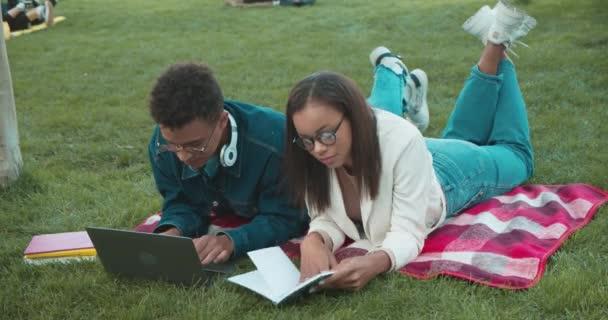 Mladý pár studentů, kteří se společně připravují na univerzitní zkoušku, leží v parku