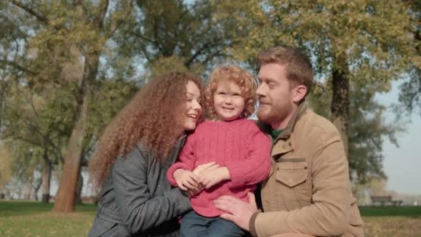 Radostní rodiče líbají děti na tváře, starají se o syna, šťastnou rodinu, lásku