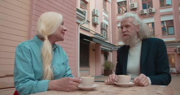 Výstřední senior šťastný pár mluvit a pít kávu na terase restaurace