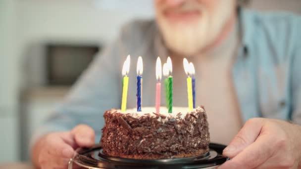 Idős ember elfújja gyertyák születésnapi torta, ünnepli az élet esemény, hagyomány