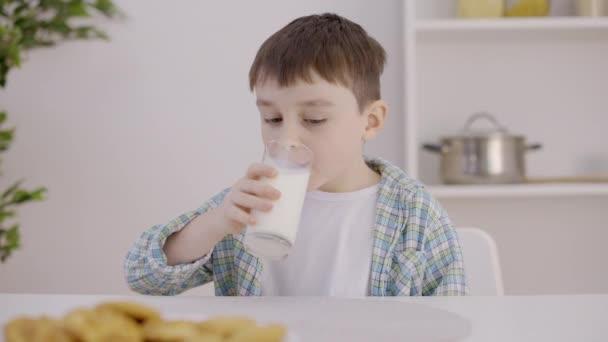 Usměvavý chlapec pije mléko ze skla, zdraví kostí, vitamínů a minerálů