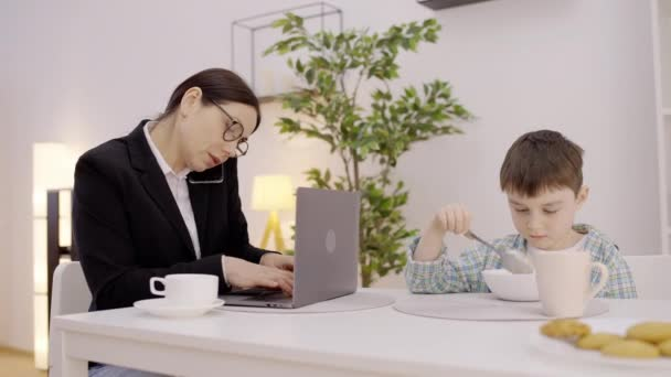 Working mother talking on phone, ignoring lonely son, eating breakfast at table