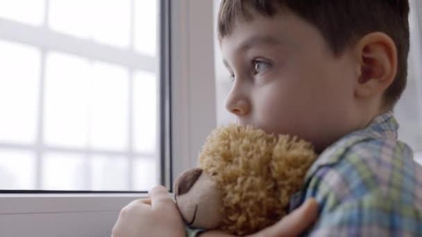Kisgyerek kezében játékmackó játék, néz ki az ablakon, eltűnt család, örökbefogadás