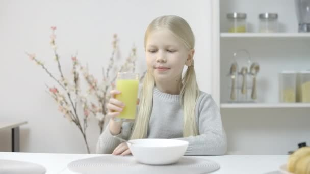 Young girl drinking fresh juice and smiling, healthy nutrition and vitamins