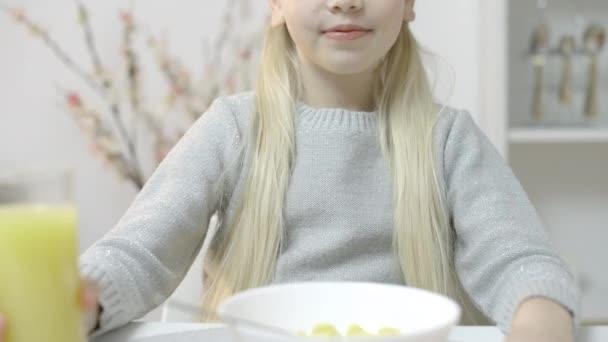 Young girl enjoying fresh juice, smiling during breakfast, healthy balanced meal