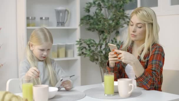 Mother and female kid using smartphones during breakfast, gadget addiction