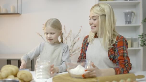 Happy family cooking together, daughter pouring flour, helping mother in kitchen