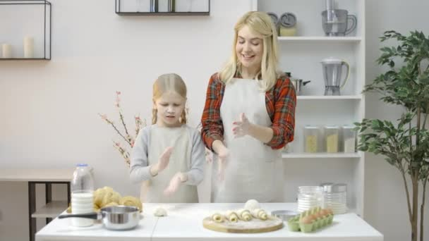 Smiling blond mom and daughter baking together, shaking off flour from hands
