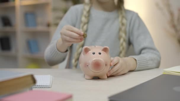 Little girl with braids putting coins in piggy bank, saving money, economy
