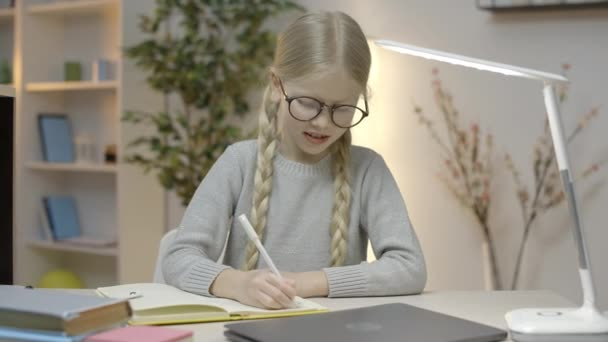 Young girl in glasses making notes in diary, doing homework, distance learning