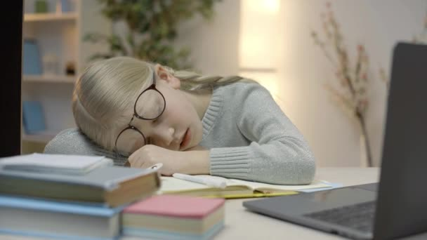 Tired girl in glasses sleeping on workbook, distance education during pandemic