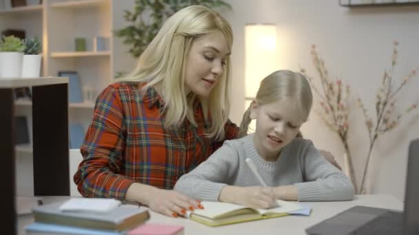 Caring mother helping little daughter to do homework, distance education