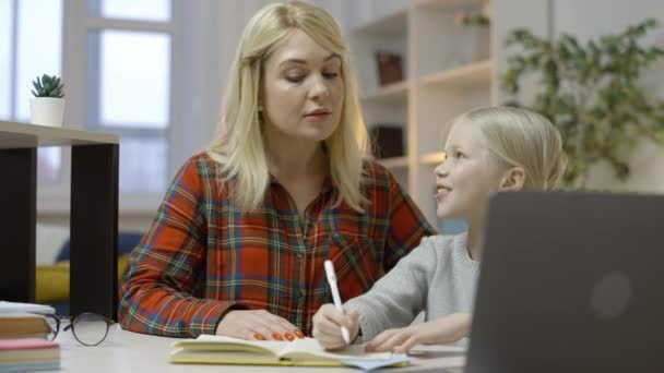 Kind mother helping smiling daughter with homework, distance education