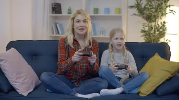 Excited mom and daughter playing video games at home, celebrating victory, fun