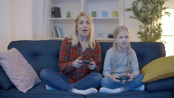 Little daughter celebrating video game victory, mother pretending to be sad