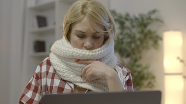 Sick blond lady in scarf coughing and working on laptop, freelance and pandemic