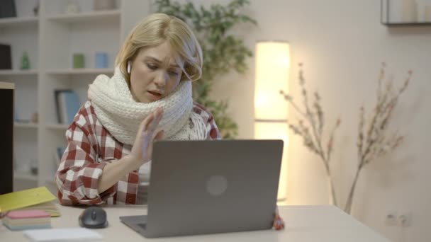 Sick freelancer in scarf waving hand on laptop camera, having video conference
