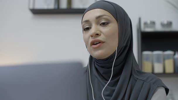 Arabische Geschäftsfrau kommuniziert mit Kunden auf Laptop, Online-Videokonferenz
